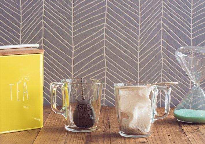 boite de thé jaune cuillère en procelaine, tasses avec filtres et sablier sur table en bois Colors of tea