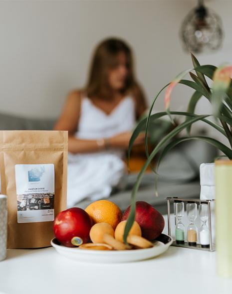 tasse de thé, sachet sablier et boite de thé, fruits sur table avec femme qui lit en arrière plan