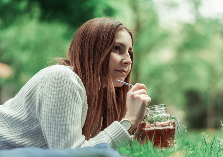 femme buvant thé dans l'herbe