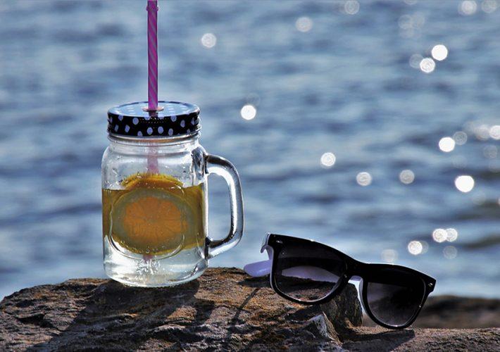 bocal boisson citron lunettes de soleil sur rocher en bord de mer