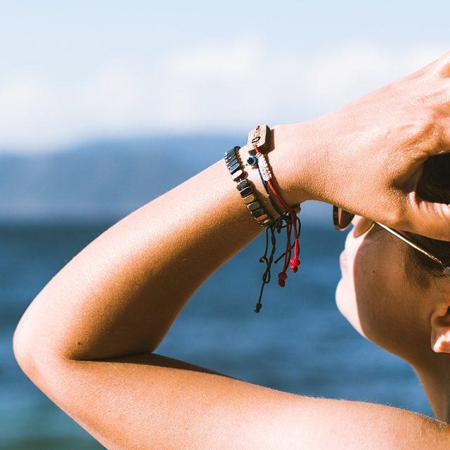 femme bronzée qui se passe la main dans les cheveux l'été