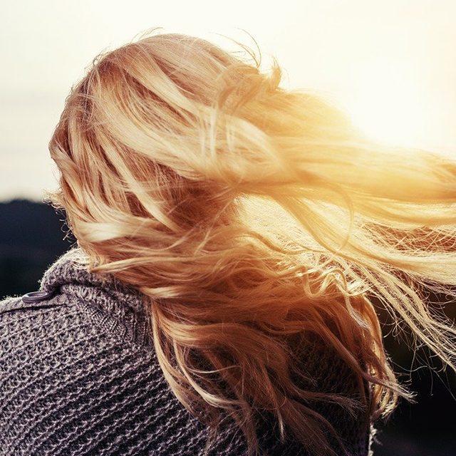 femme de dos, cheveux blonds au vent