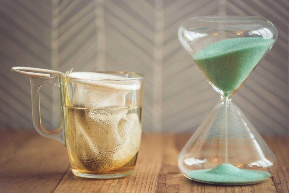 tasse avec filtre chaussette et sablier sur table en bois