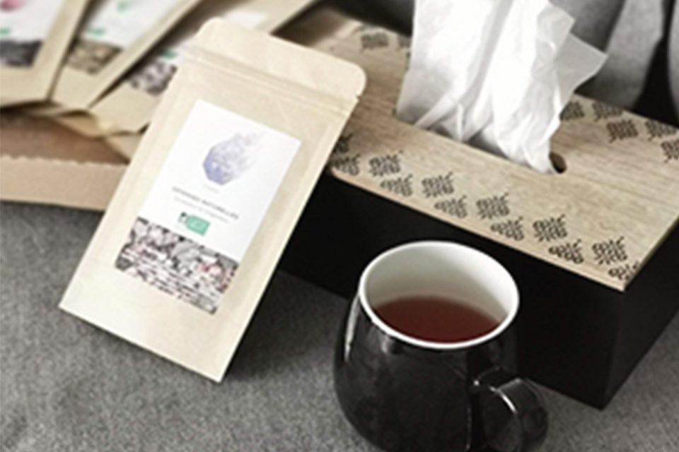 tasse de thé, boite de mouchoirs et sachet thé sur canapé gris
