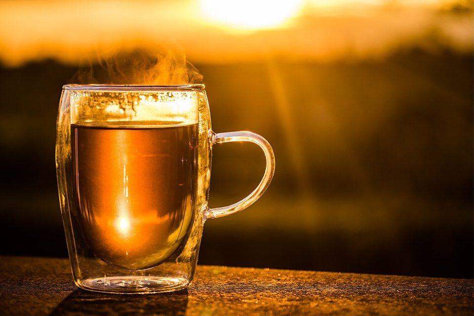 tasse de thé fumante sur fond de coucher de soleil