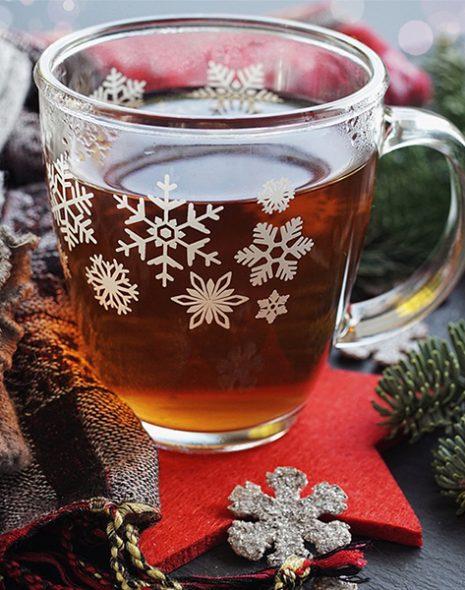 tasse de thé de noel avec branche de sapin écharpe et étoiles