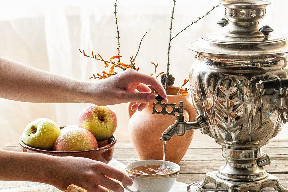 une personne se sert une tasse de thé au samovar