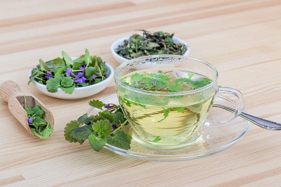 tasse de thé translucide avec thé en vrac dans soucoupe et cuillère en bambou