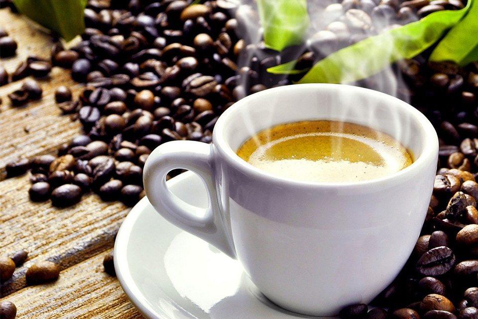 tasse de café fumante sur table en bois avec grains de cafés