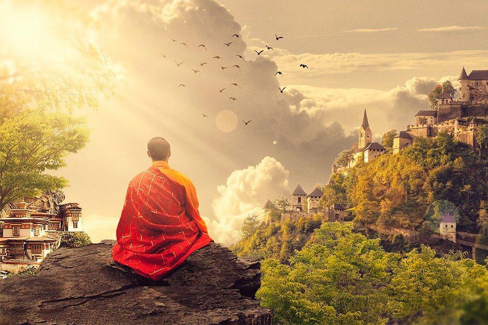 moine bouddhiste méditation sur rocher surplombant temple