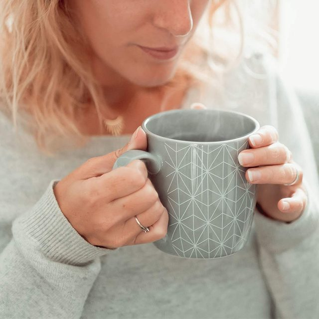 tasse fumante dans mains de femme en pull gris colors of tea