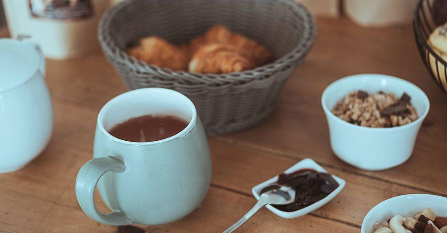 tasse de rooibos sur table en bois et petit déjeuner, rooibos gourmand colors of tea