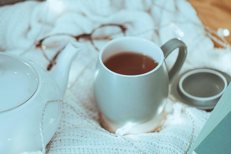 tasse de thé sur plaid blanc théière et lunettes