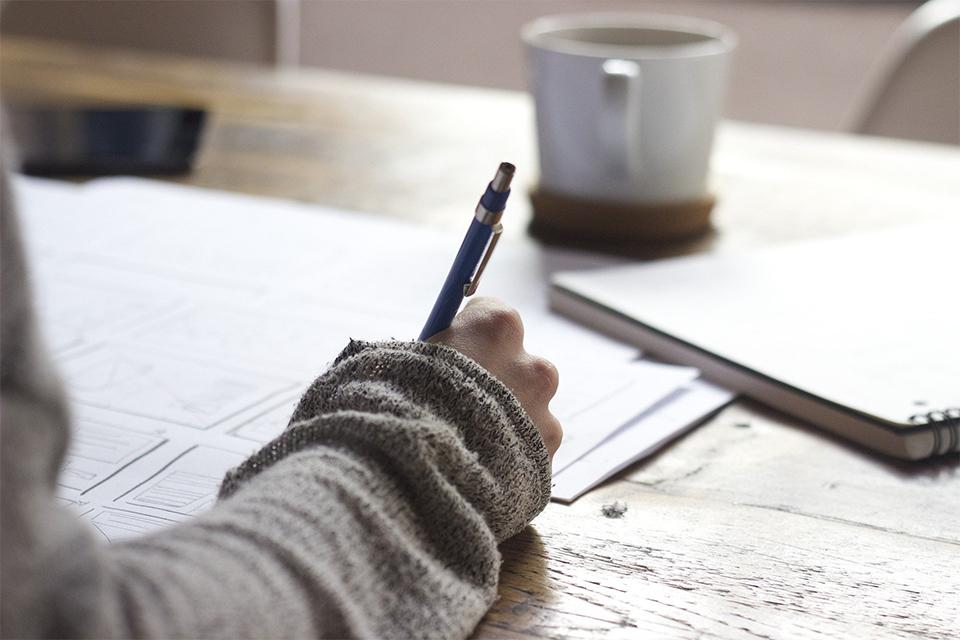 femme qui écrit sur une table en bois avec une tasse de thé. Les bienfaits du maté pour la concentration