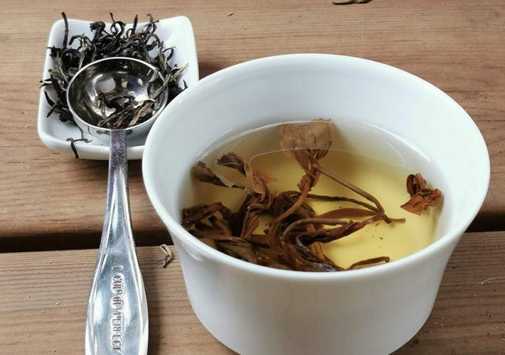 thé jaune dans coupelle et feuilles de thé jaune avec cuillère à thé colors of tea