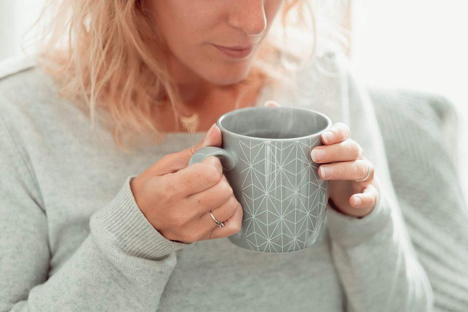 tasse fumante dans mains de femme, les bienfaits du rooibos pour le corps, thé rouge sans théine colors of tea